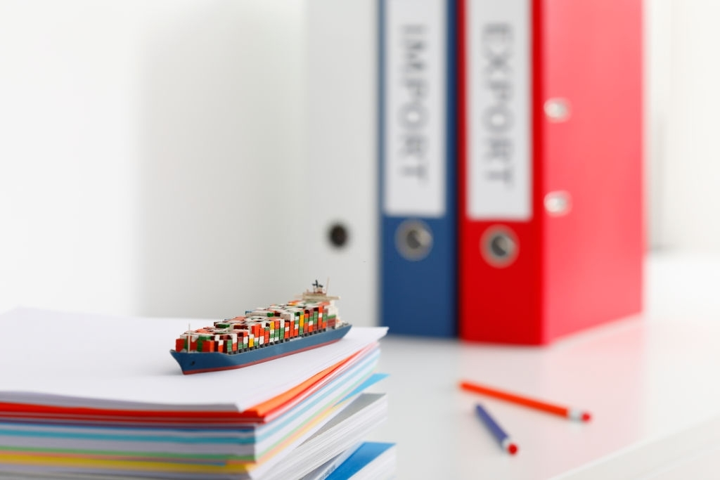 Self-made miniature model of a container ship in front of two folders
